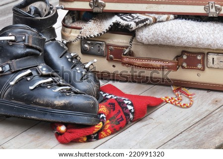 small open suitcase full of warm clothes with old ski boots  - stock photo