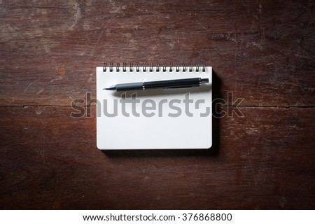 Small opened notepad with blank area for text or message and pen on rustic wood table with low key scene.