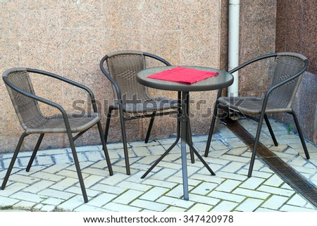 small outdoor cafe near the wall of the building with a single table with three chairs - stock photo