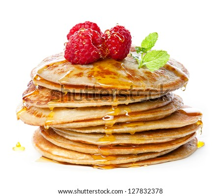 Small pancakes topped with honey, raspberries and mint on white background - stock photo