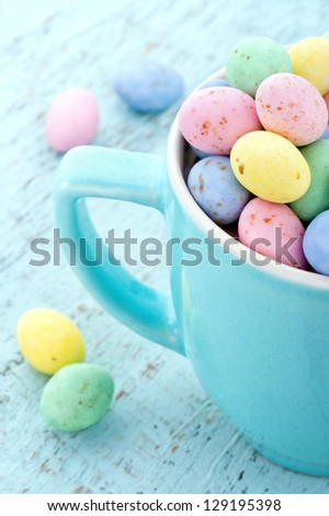 Small pastel easter eggs in a light blue cup on vintage wooden background - stock photo