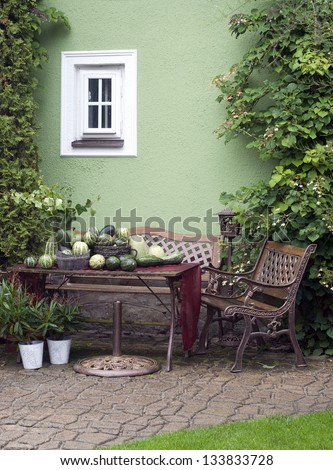 Small patio or street garden with rustic chair and table, green vegetable and plants. - stock photo