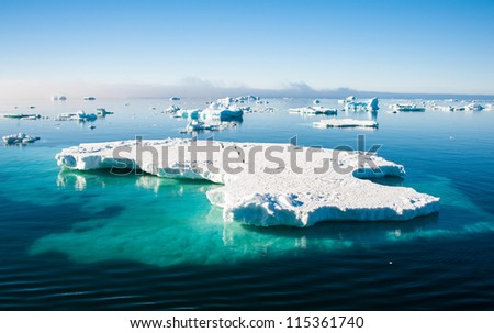 Small penguins on the huge iceberg in Antarctica - stock photo