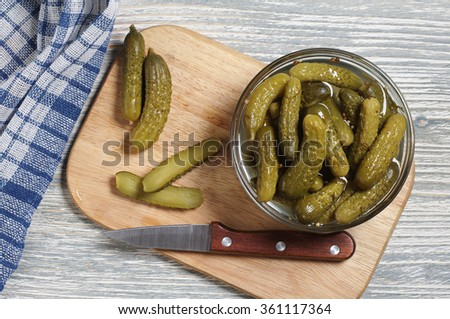 Small pickled cucumbers in bowl on old wooden table, top view - stock photo