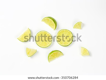 small pieces of fresh lime on white background - stock photo