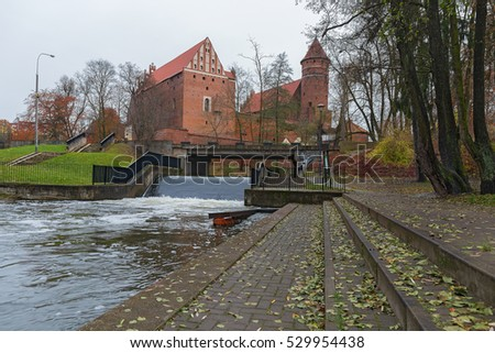Small pier on the river in the center of the town. Ancient castle on the background.