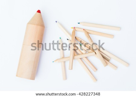 small pile of crayons and one huge crayon - stock photo