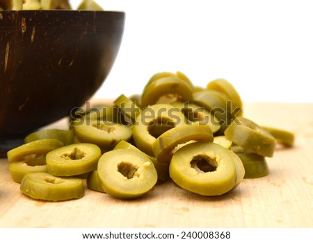 Small pile of sliced green olives isolated and wooden bowl on chopping board on the white background  - stock photo