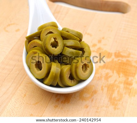 Small pile of sliced green olives isolated in white spoon on chopping board on the white background  - stock photo