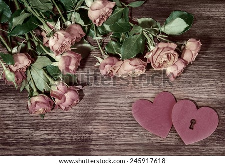 Small pink garden roses  and hearts on wooden surface. Retro style romantic floral background. Valentines day background. - stock photo