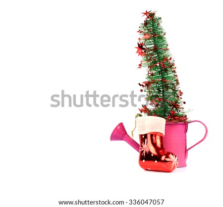 Small pink watering can filled with Christmas decorations isolated on white. Free space for text