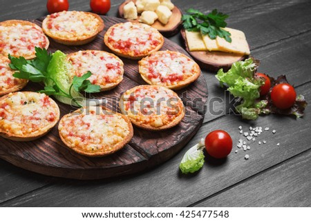 Small pizza with mozzarella cheese, sausage, ham, parsley, lettuce, cherry tomatoes in the olive wood planks on a dark black wooden background - stock photo