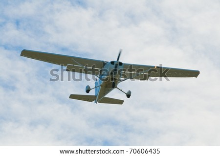 Small plane descending against a cloudy sky