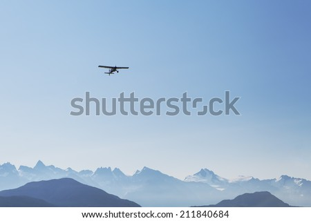 Small plane flying over hazy mountains in Southeast Alaska with bright blue sky.