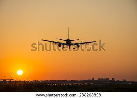 Small plane landing at dusk. - stock photo