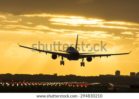 Small plane landing during sunrise. Plane is blown off his route. - stock photo