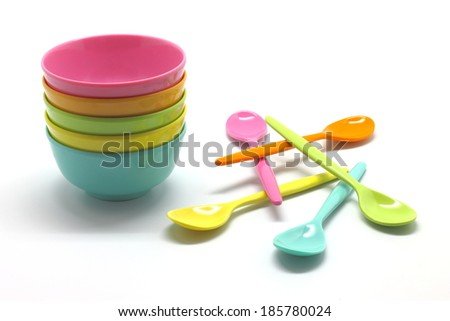 Small plastic bowls and spoons isolated on white background  - stock photo