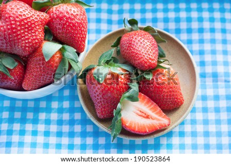 Small plate and bowl filled with succulent juicy fresh ripe red strawberries on table with blue checkered tablecloth - stock photo