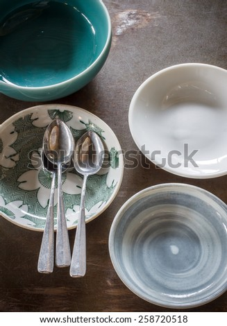 small plate and vintage spoon put on grunge table, still life image dark tone - stock photo