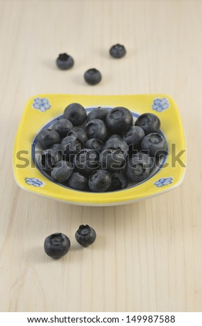 Small plate with delicious berry of blueberry on light wooden background. Concept of organic eating. - stock photo