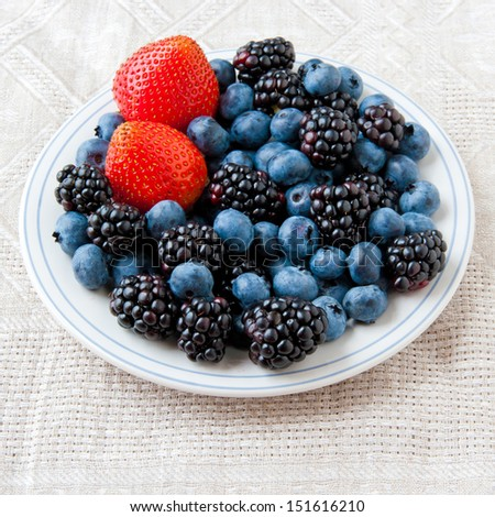 Small plate with fresh summer berries - strawberry, blueberry and blackberry. - stock photo