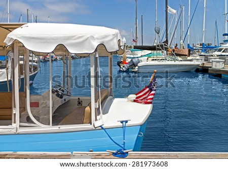Small pleasure boat with white canopy docked in marina. Flag with anchor. Motorboats, blue water and sky background.  - stock photo