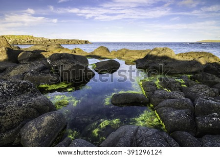 Small Pond of Sea Water covered in green algae and surrounded by Volcanic Rocks. Faroe islands, Denmark, Europe - stock photo