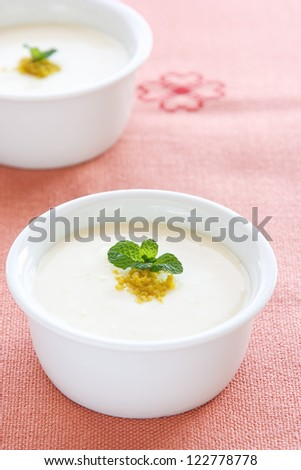 Small pot of lime mousse topped with grated lime and fresh mint over a salmon table cloth. - stock photo