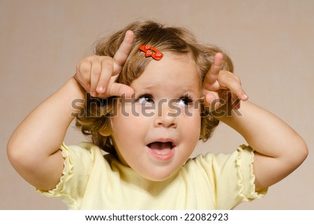 Small pretty girl making horns with fingers - stock photo