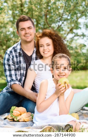 Small pretty girl sitting in the foreground on a plaid smiling and holding a big green apple while her happy parents on a background hugging and smiling, selective focus - stock photo