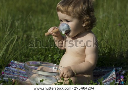 Small pretty male child with curly hair sitting in lawn on green grass eating cream of wheat from glass plate with spoon sunny day, horizontal picture - stock photo