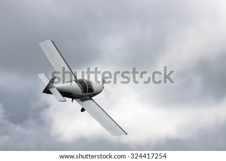 Small private plane flying under stormy clouds
