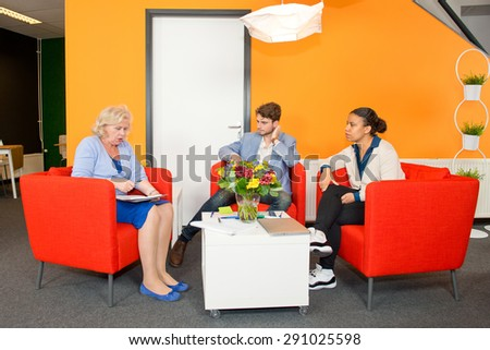 Small project team meeting in a stylish, modern lobby of an office building, between two young associates and a senior reintegrated woman. - stock photo