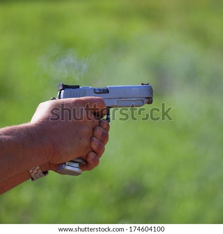 Small puff of smoke coming from a handgun after being fired - stock photo
