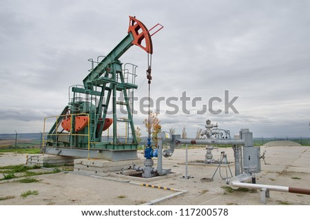 Small pump jack mining crude oil - stock photo