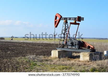 Small Pumpjack in agricultural field - stock photo