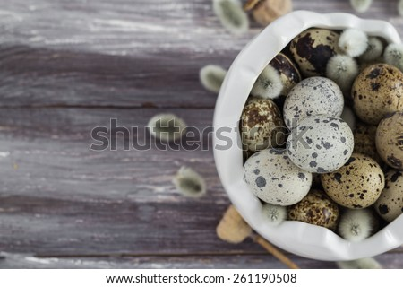 Small quail eggs in a dish on a wooden table. Scattered database. - stock photo