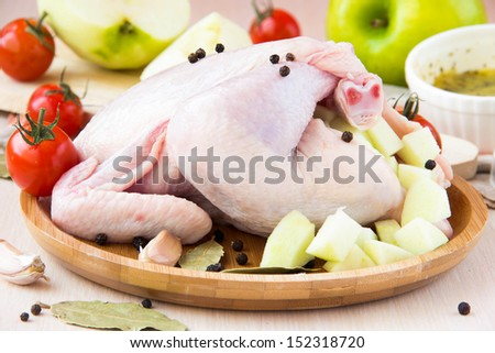 Small raw chicken stuffed with green apples and prepared for baking on wooden plate - stock photo