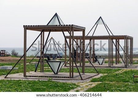 Small recreation park close to the seashore with wooden cubes and iron pyramids.