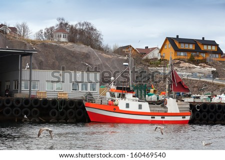 Small red and white fishing boat stands moored in Norway - stock photo