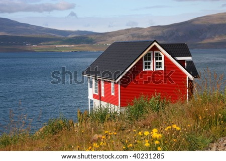 Small red generic home next to Hvalfjordur fiord in Iceland. Typical Nordic residential architecture.