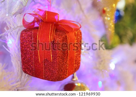 Small red gift box on the christmas tree in the cristmas night. - stock photo