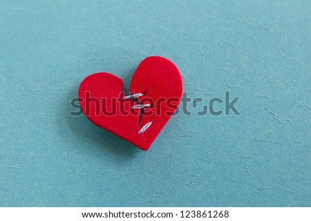 small red heart, broken with threaded stitches - stock photo