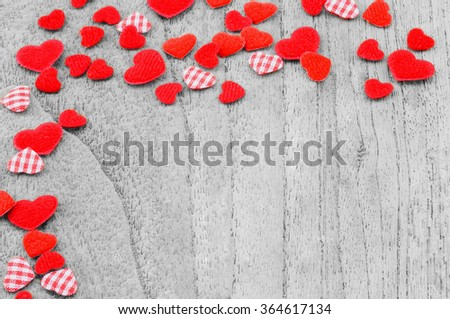 Small red hearts putting on monochrome wooden background