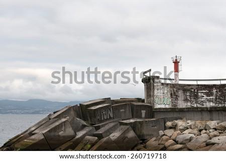 Small red lighthouse in Portonovo in Galicia, Spain. - stock photo