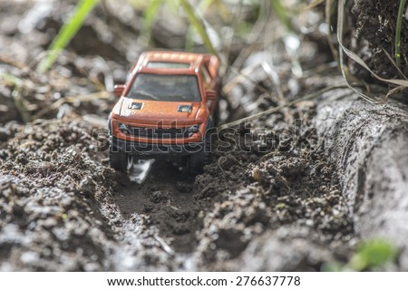 Small red off road car toy in the nature. Miniature - stock photo