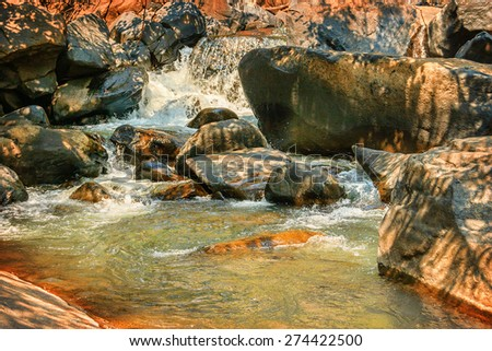 Small river with thresholds flowing through red stones of the tropical Indian jungle
