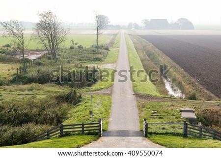 Small road in hazy Frisian polder landscape in countryside near Harlingen, Friesland, Netherlands - stock photo