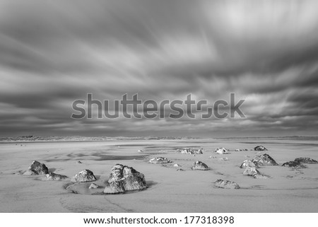 Small Rocks on the Beach with a Dramatic Sky. Processed in Monochrome  - stock photo