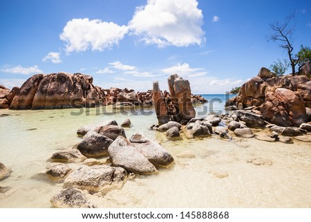 small rocky island in the sea under a blue sky with some white clouds, Seychelles - stock photo